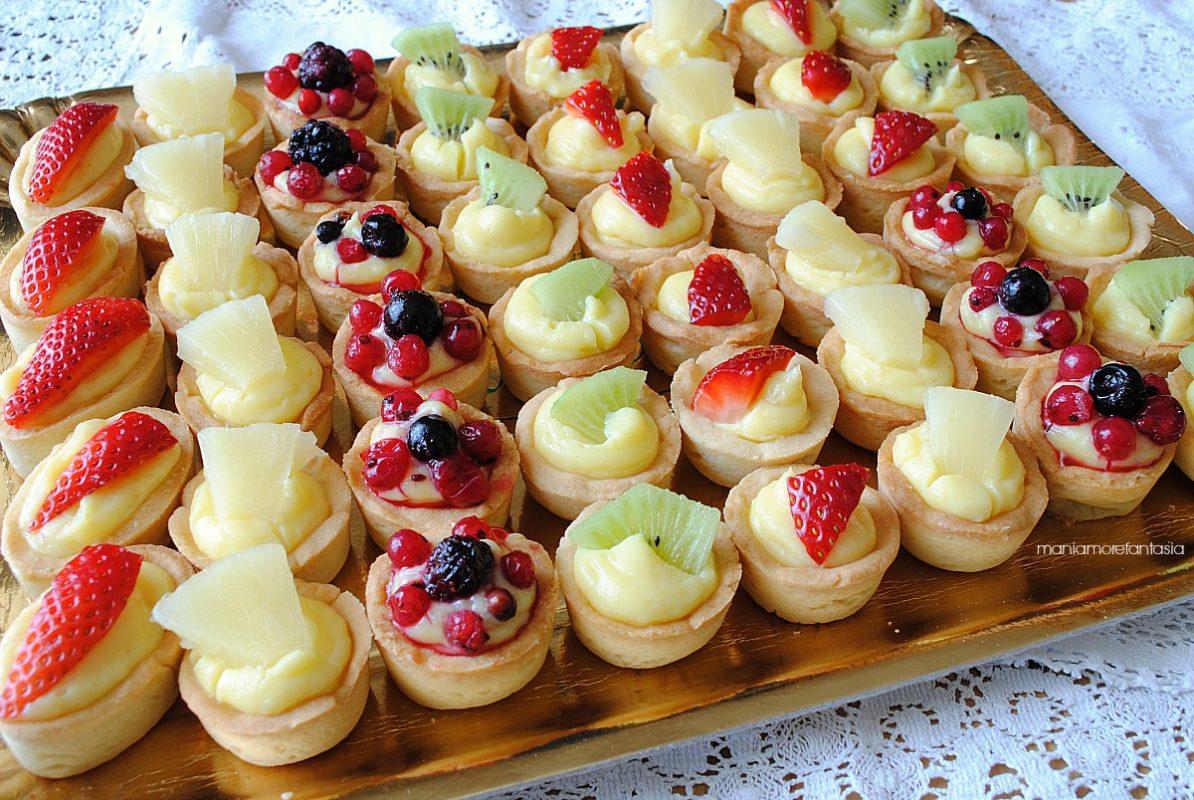 Tartellette alla crema con frutta. Contenitori di pasta frolla o sfoglia ripieni di crema pasticcera e ricoperti da frutta in pezzi.
